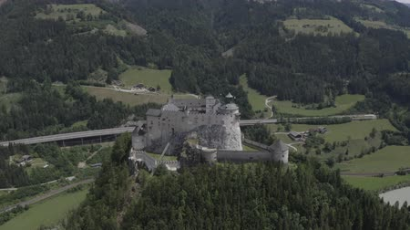 王 : Aerial pan up view of Hohenwerfen Castle, Austria. Medieval rock fortress in Alpine mountains with spruces. Overlooking the Werfen town in Salzach valley. Summer 動画素材