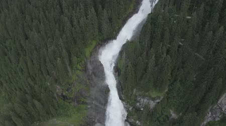 curso : Aerial view of Krimml waterfall Cascades. Drone flight above strong water flow on rocks in spruce forest. Rainbow Tirol, Salzburg land, Austria.