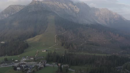 dolomitok : Aerial view of Tyrol village in Dolomites. Rural landscape from drone. Geisler or Odle Dolomites Group, forest with chopped pine trees, farming houses, South Tyrol, Italy.