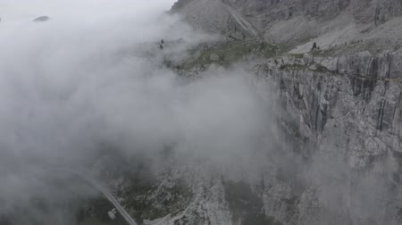 arborizado : Aerial view of winding road with going cars along mountain foot. Drone flies through clouds to sheer cliffs, Dolomites, South Tyrol, Italy. Vídeos