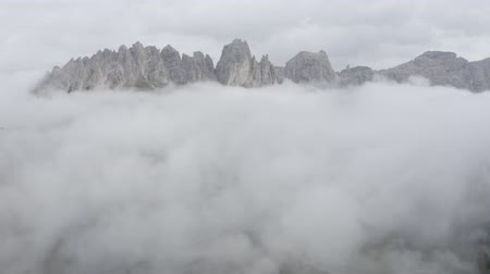 arborizado : Aerial zoom in pan up view of Dolomites mountains. Drone flies through clouds to mountain peaks. Costalunga, South Tyrol, Italy.