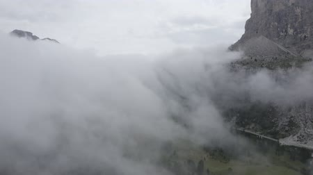 arborizado : Dolomites, Alps mountains. Aerial view of sheer cliffs, mountain peaks through clouds. Summer cloudy weather. Geisler or Odle Dolomites Group. South Tyrol, Italy. Stock Footage