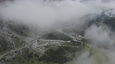 dolomitok : Aerial view of Dolomites valley. Drone flies to sheer cliffs through clouds above green meadows, spruces, cars driving on road along mountain foot. Geisler or Odle Dolomites Group. South Tyrol, Italy. Stock mozgókép