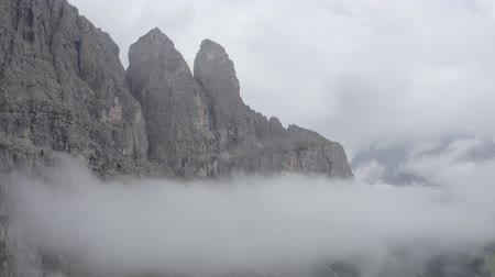 tirol : Aerial zoom in view of Dolomites mountains. Drone flies through clouds to mountain peaks. Costalunga, South Tyrol, Italy.
