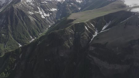 Грузия : Aerial view of green mountainous range with snowy peaks in Kazbegi, Georgia. Discover the earth. Nature of planet. Стоковые видеозаписи
