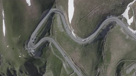 georgien : Aerial view of cars driving on winding road in mountains. Kazbegi, Georgia. People flying on paraglider or paraplane. Summer landscape. Snow lies in parts on the ground. Travel motivation. Journey. Videos