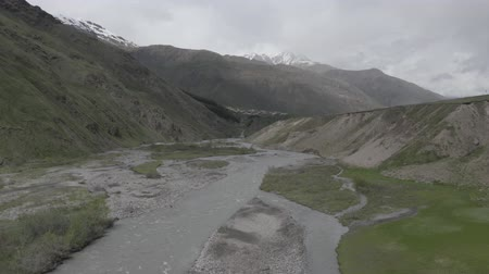 enrolamento : Drone flies over the river with a flow of river water in mountains. Aerial view of landscape in Kazbegi, Georgia.