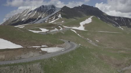 georgien : Aerial view of cars driving on winding road in mountains of Kazbegi, Georgia. Summer landscape. Mountains with snow. Snow lies in parts on the ground. Travel motivation. Journey.