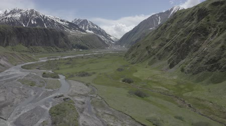 georgien : Aerial view of mountains valley with river, snowy mountain peaks, green meadows, fields in Kazbegi, Georgia. Zoom in. Videos