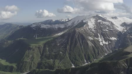 enrolamento : Aerial view of green mountainous range with snowy peaks in Kazbegi, Georgia. Discover the earth. Nature of planet. Vídeos