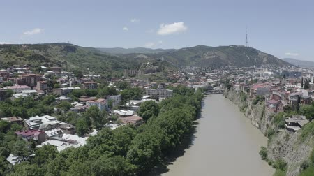 georgien : Aerial view of Kura river in Old Town of Tbilisi, Georgia. Church, historic houses, trees, mountain and blue sky. Summer Travel destinations. D-log. Videos