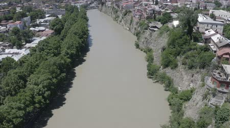 grúzia : Aerial view of Kura river in Old Town of Tbilisi, Georgia. Church, historic houses, trees, mountain and blue sky. Summer Travel destinations. D-log. Stock mozgókép