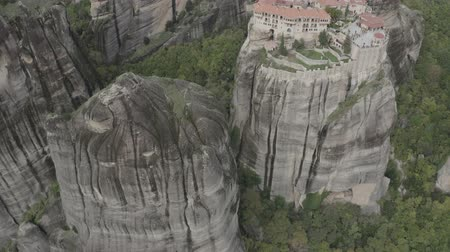 enrolamento : Aerial view of Meteora with historical orthodox monasteries on top of meteors cliffs, Kalabaka, Greece. Drone flies over beautiful mountainous landscape with rocky cliffs. Vídeos