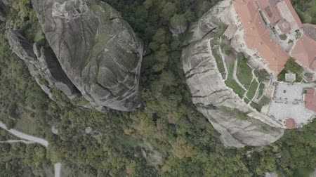 enrolamento : Aerial top down view of Meteora with historical orthodox monasteries on top of meteors cliffs, Kalabaka, Greece. Drone flies over beautiful mountainous landscape with rocky cliffs.