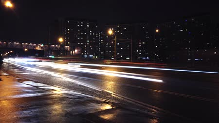 marnost : Moscow, Russia - JANUARY 10 2020: Time lapse. Moscow. Cars with headlights driving on the highway in the night, dark evening, Block houses with light in windows. Bridge over road. Flashlights on street. People stand on bus stop.