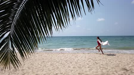 divertirsi : Young lady in red swimming suit, long white dress, sun glasses runs on sandy beach coastline near sea, foaming waves. View through palm leaf. Happy summer holidays. Beach resort. Super slow motion. Filmati Stock