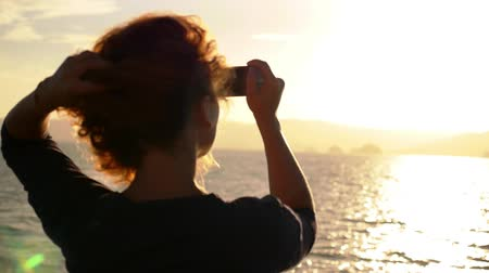 cabeça e ombros : Young Curly Woman Taking a Photo of Amazing Sunrise from the Ship. Sea Voyage in Thailand. Koh Samui. Slow Motion.