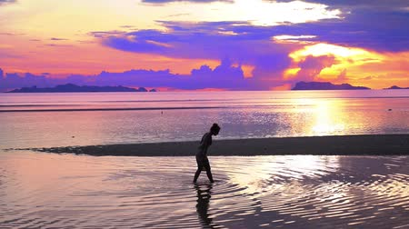 um : Amazing Sunset and Silhouette of a Girl Walking Alone. Beautiful seascape in Thailand, Koh Samui.