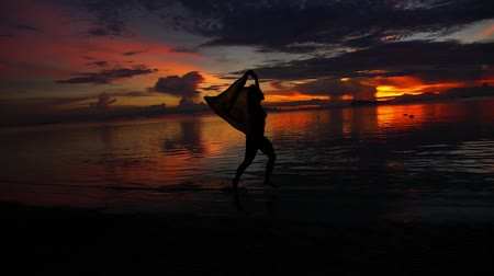 atividades : Silhouette of a Girl Running down the Beach at Epic and Beautiful Sunset.  Slow Motion. Thailand. Koh Samui. Stock Footage