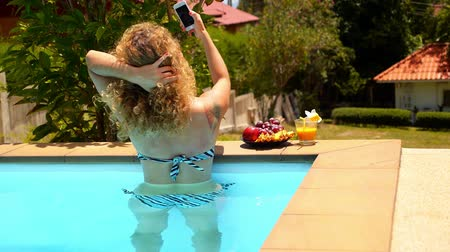 kudrnatý : Beautiful Woman with Curly Hair Making Selfie in the Swimming Pool during Summer Holidays.