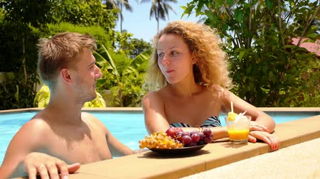 медовый месяц : Happy Smiling Couple Eating Fresh Fruits Together in Azure Swimming Pool near Resort in Thailand, Koh Samui. Стоковые видеозаписи