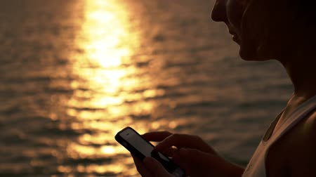 eszköz : Close up on Young Woman Surfing Internet, Checking Social Networks on the Cell Phone against Amazing Seascape during Sunset. Slow Motion. Stock mozgókép