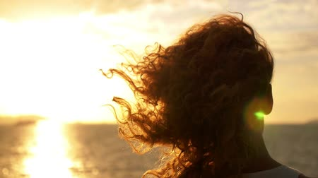 hareketli : Young Woman with Curly Hair and Tattoo Standing against Impressive Spectacular Sunset on the Yacht. Slow Motion.