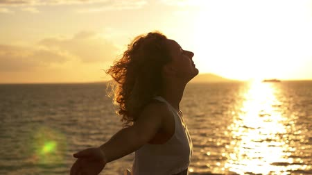 estilo de vida saudável : Motivational Uplifting Slow Motion Video. Happy Young Curly Woman Spreading Arms at Spectacular Sunset. Sea Voyage in Gulf of Siam. Thailand.