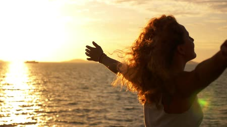 глубоко : Young Happy Girl with Curly Hair and Tatto Spreading Arms at Beautiful Sunset. Sailing on the Ferry. Motivating Inspiring Slow Motion Video. Стоковые видеозаписи