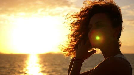 motivasyonel : Young Woman with Funny Curly Ginger Hair Smiling and Admiring the Sunset over Deep Sea. Motivational and Inspiring Slow Motion Video. Thailand.