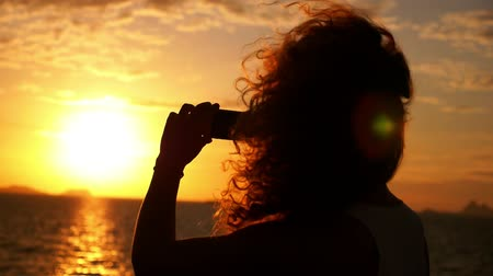 fotografando : Young Woman Taking Pictures of Sunset with Smart Phone while Sailing on the Yacht. Close up of Camera Phone Photographing Amazing Seascape. Slow Motion.