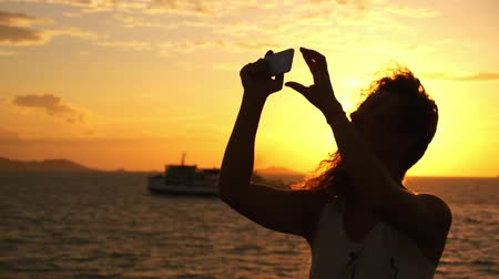 emocional : Attractive Young Woman with Curly Hair Taking Selfie against Impressive Sunset during Sea Cruise. Slow Motion. Thailand. Gulf of Siam.