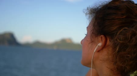 motivasyonel : Motivational Uplifting Close Up Video of Young Beautiful Woman Enjoying Music On Earphones. Sea Voyage in Thailand. Slow Motion. Stok Video