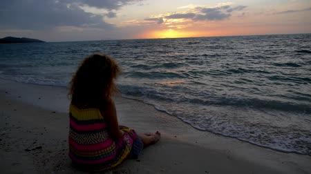 kudrnatý : Young Woman with Curly Hair and Tattoo in Bright Dress Sitting Alone on the Beach at Sunset. Vacation in Tropical Thailand. Slow Motion.