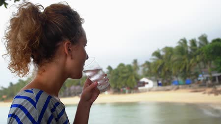 içme : Woman in Beach Cafe Drinking Water. Seashore with Palms. Tropical Rainy Day. Low Season in Thailand. Koh Samui. Stok Video