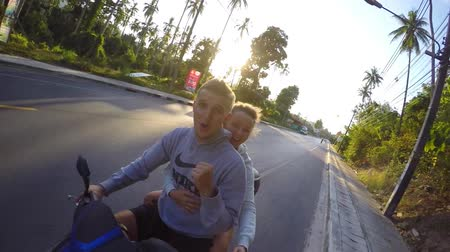 humor : Cheerful Beautiful Couple Riding Scooter Together at Sunset on Tropical Island of Koh Samui, Thailand. Slow Motion. HD, 1920x1080. Stock mozgókép