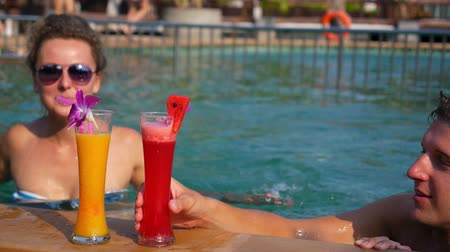 gyümölcslé : Healthy Young Couple Drinking Fresh Juices in Swimming Pool. HD, 1920x1080. Stock mozgókép