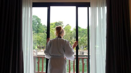 perdeler : Woman in Bathrobe Opening Window Curtains at Hotel Room. HD, 1920x1080.