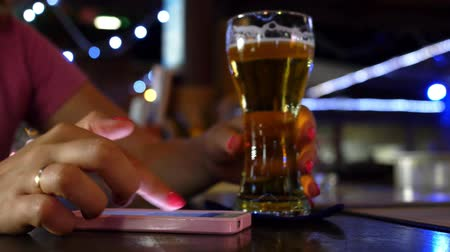 bares : Hand Using Mobile Phone with Glass of Beer at a Bar. Closeup. HD, 1920x1080.