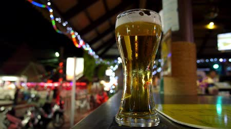 beer tap : Glass of Foamy Fresh Draught Beer on Bar Counter on Night Street. Closeup. HD, 1920x1080. Stock Footage