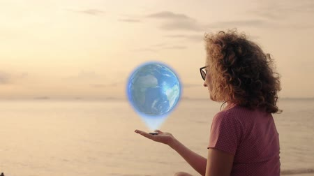 telekomünikasyon : Peaceful Woman with Earth Hologram in hand on beach.  glowing and shining futuristic interface. Stok Video