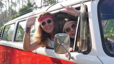 hippi : Hippie Girls Travel in Van on a Road Trip with Peace Sign Stock mozgókép