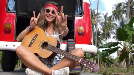 saç bantı : Young Hipster Hippie Woman Sitting on Road with Guitar Stok Video
