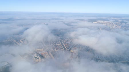 brisé : Winter drone shot above the clouds of the Minsk city snow sunny day residential buildings aerial
