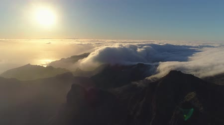 moscas : Aerial view of mountains and fog creeping the cliffs on sunset in Tenerife, Canary islands, Spain