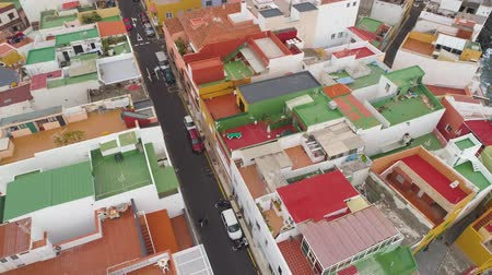 kanári : TENERIFE, PUNTA BRAVA, SPAIN - MAY, 18, 2018: Aerial view colorful houses of small town on the coast Stock mozgókép