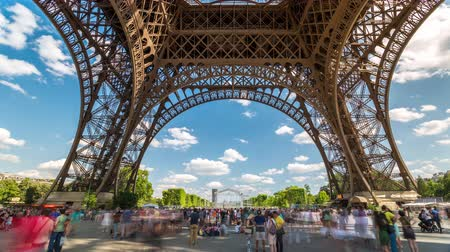típico : PARIS, FRANCE - JUNE 19, 2018: Eiffel Tower day timelapse with people walking around. Sunny day.