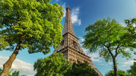 típico : PARIS, FRANCE - JUNE 19, 2018: Eiffel Tower day timelapse. Sunny day with clouds. Green trees.