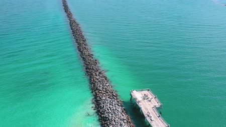 golfbreker : Aerial drone panorama view flight over Miami beach. Breakwater pier and sea from above. Stockvideo