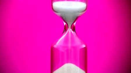 hora : Hourglass against pink background-close up